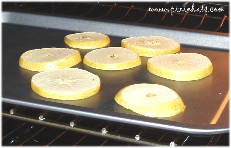 Drying out apple slices in the oven to make the yule garland